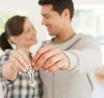 Happy couple holding keys to their new house